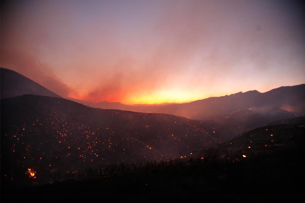 16. Дым поднимается на холме на фоне света от пламени лесного пожара в Актоне, Калифорния, 30 августа 2009 года. (REUTERS/Mario Anzuoni)