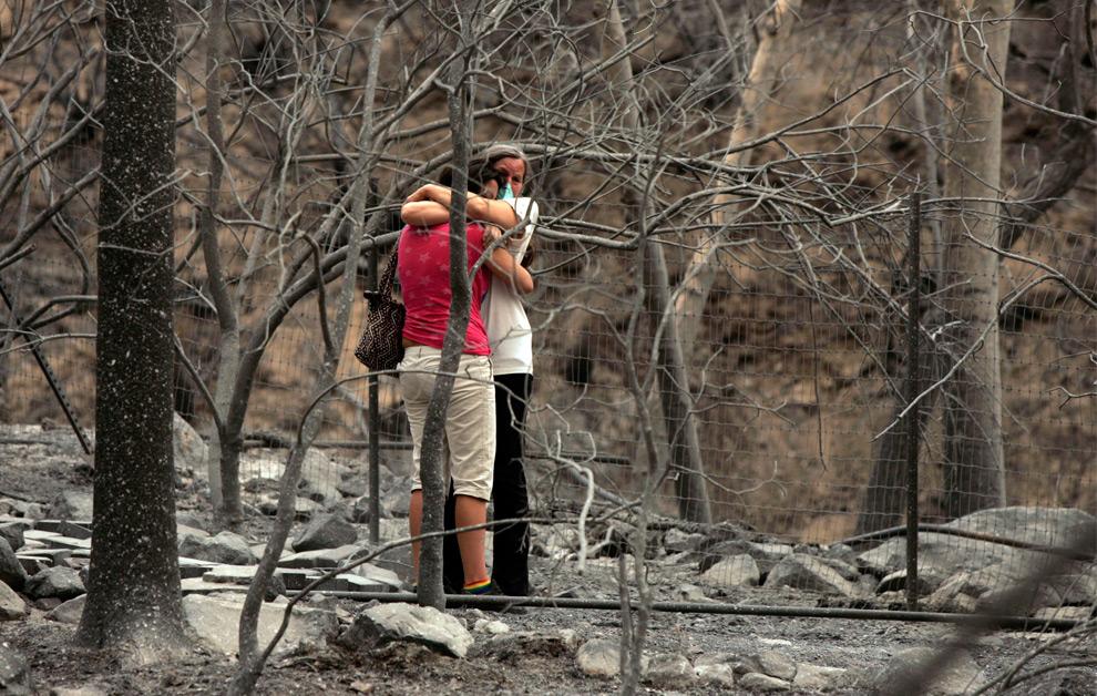 17. 59-летняя Джули Гарсия обнимает свою 19-летнюю дочь Джесси во вторник 1 сентября 2009 года, после того, как ее дом был уничтожен лесным пожаром, который прошел по соседству в Туюнге, штат Калифорния. (AP Photo/Los Angeles Times, Irfan Khan)