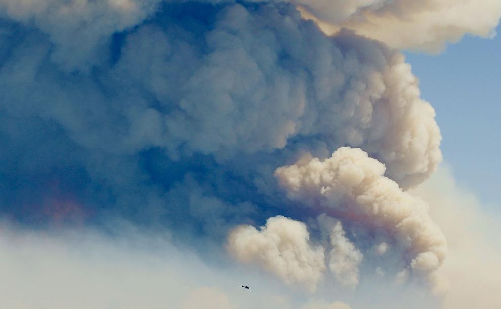18. Еле видимый вертолет на фоне огромного облака дыма от лесного пожара над Национальным Калифорнийским заповедником 31 августа 2009 года в Лос-Анджелесе, штат Калифорния. (Kevork Djansezian/Getty Images)