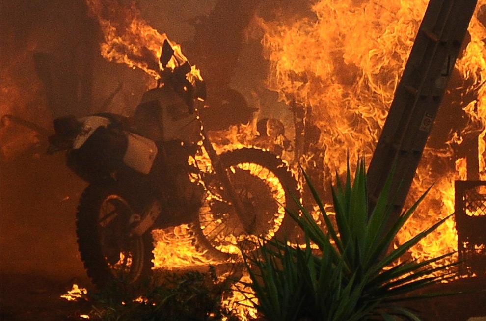 19. Мотоцикл горит в лесном пожаре в округе Большая Туюнга в Лос-Анджелесе, штат Калифорния, 29 августа 2009 года. (REUTERS/Gene Blevins)