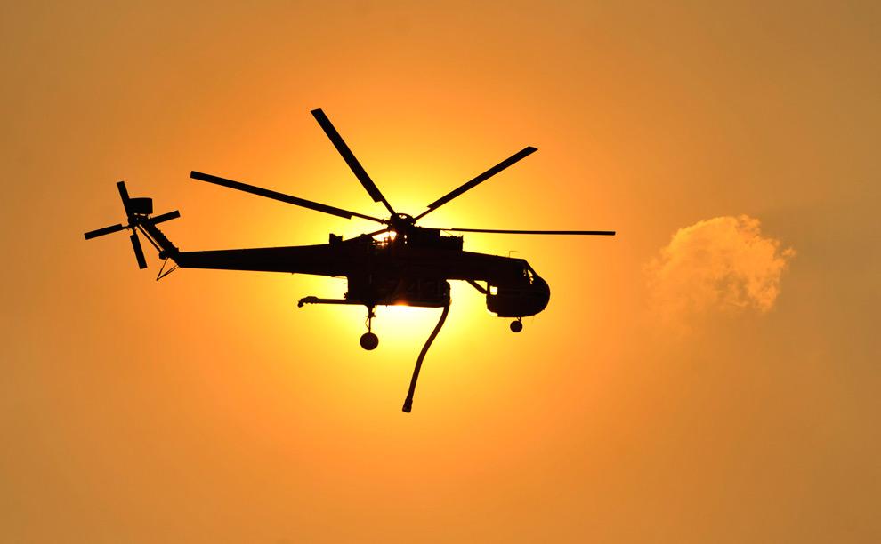 20. Вертолет с водой пролетает на фоне солнца по направлению к жилому району в Ла Кресента, штат Калифорния, во вторник 1 сентября 2009 года. (AP Photo/Jae C. Hong)