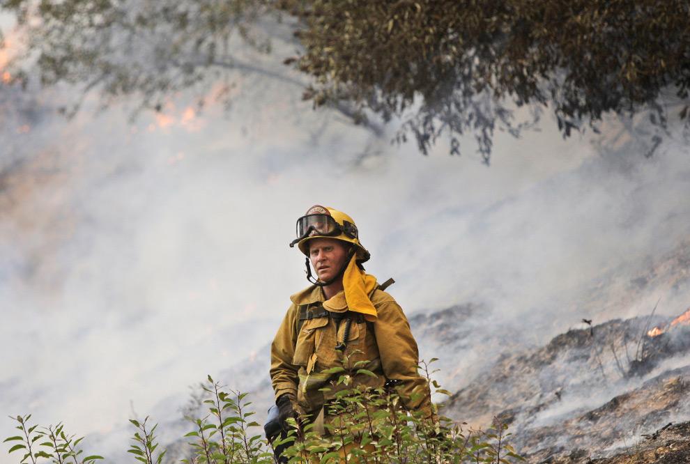 21. Пожарный выглядывает из противопожарной полосы в лесу, которая сдержала пожар в парке Deukmejian Wilderness от распространения на соседнюю территорию Ла Кресента, штат Калифорния, во вторник 1 сентября 2009 года. (AP Photo/LM Otero)