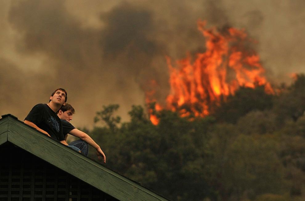 22. Два жителя района Ла Кресента смотрят на лесной пожар, сидя на крыше собственного дома, во вторник 1 сентября 2009 года. (AP Photo/Jae C. Hong)