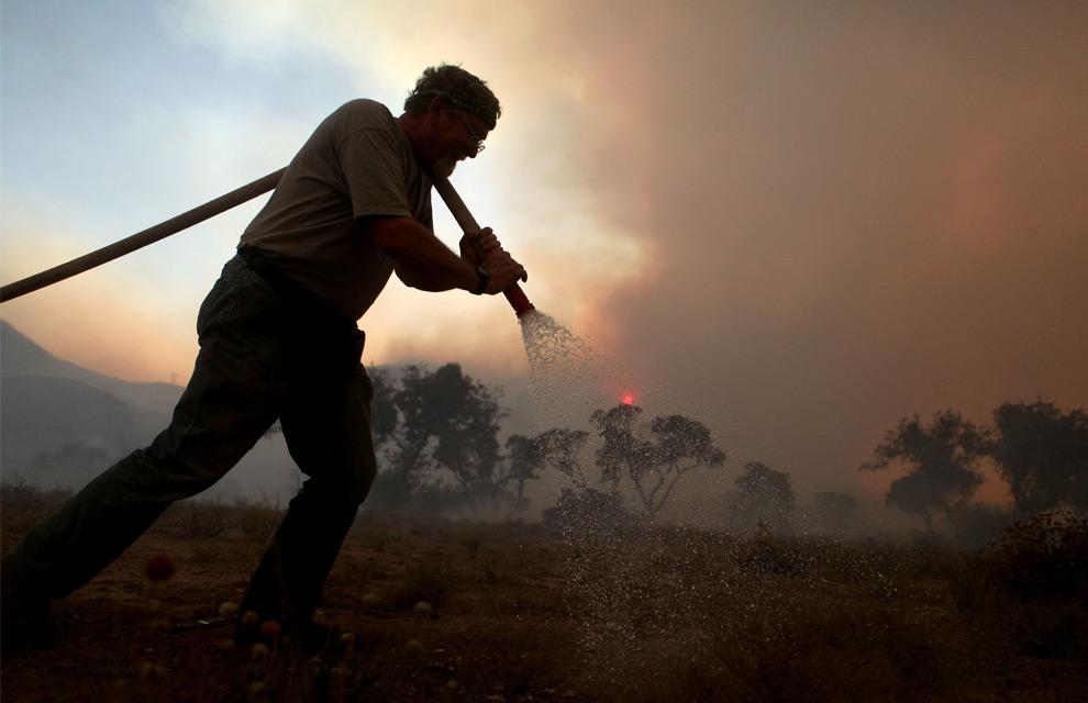 23. Тед Хамм обливает территорию из садового шланга после прошедшего в его саду лесного пожара 30 августа 2009 года в Актоне, штат Калифорния. (Justin Sullivan/Getty Images)