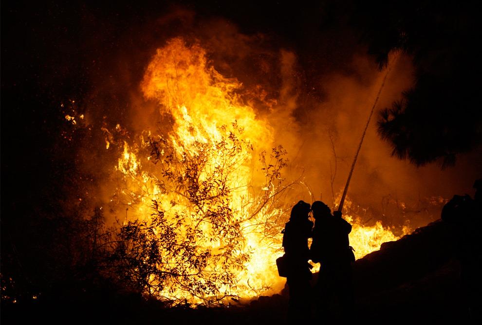 25. Пожарные работают у дома, которому угрожает лесной пожар, в Ла Кресента Грендэйл, штат Калифорния, во вторник 1 сентября 2009 года. (AP Photo/LM Otero)