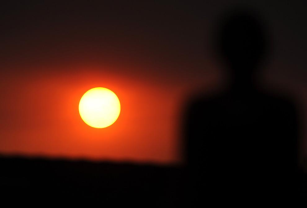 29. Солнце садится в красном небе от пожара, окутавшего Лос-Анджелес, штат Калифорния, 1 сентября 2009 года. (GABRIEL BOUYS/AFP/Getty Images)