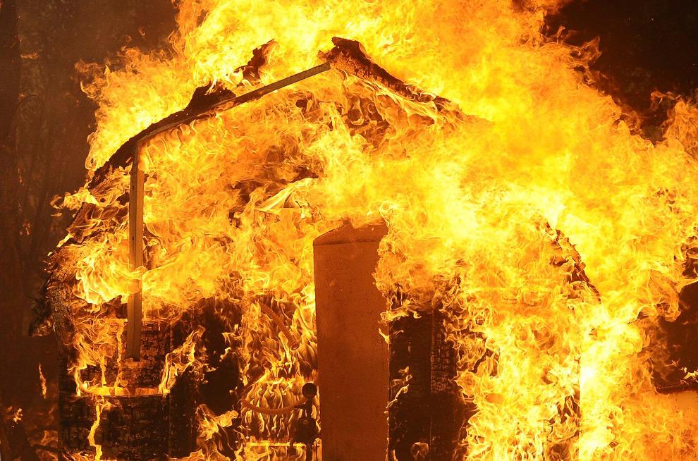 33. Маленькое неопознанное здание горит в лесном пожаре в области Большого каньона Туюнга в Лос-Анджелесе, Калифорния, 29 августа 2009 года. (REUTERS/Gene Blevins)