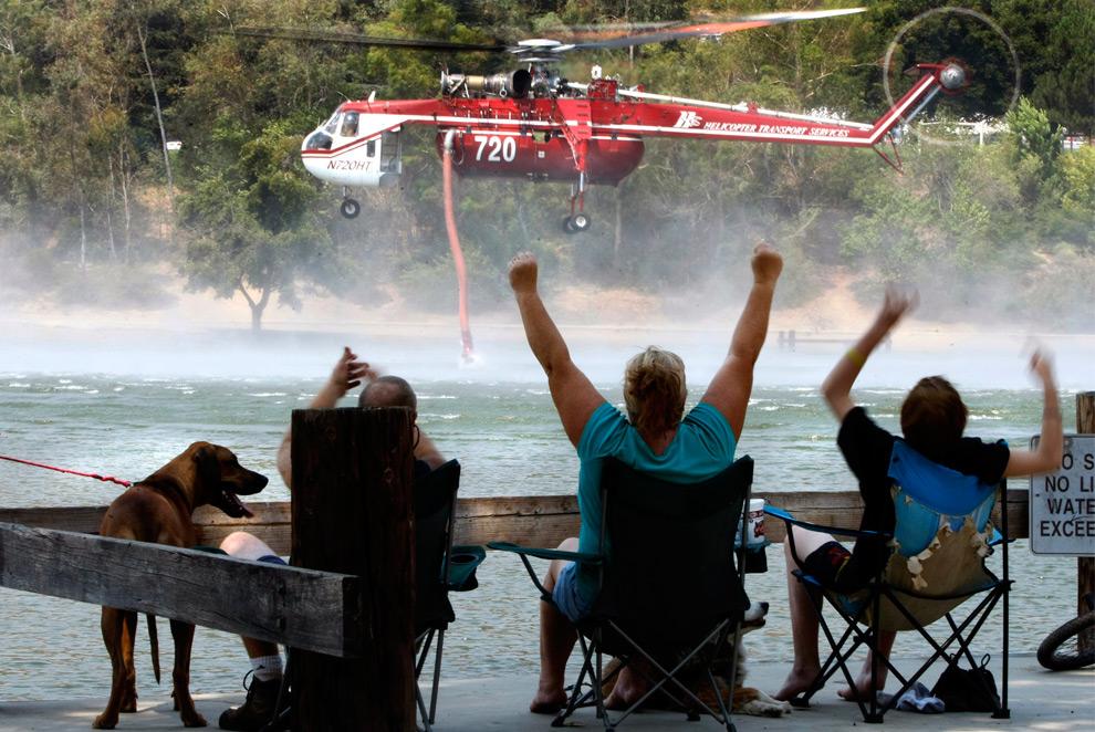 38. Семья МакГенри приветствует пожарный вертолет «Sikorsky S64 Sky Crane» с пирса в Региональном парке Юкайпа. Вертолет прилетел за очередной порцией воды во вторник 1 сентября 2009 года. Родители и сын провели ночь в парке, получив приказ об эвакуации из собственного дома. (AP Photo/Los Angeles Times, Don Bartletti)