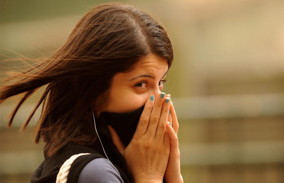 12) Девушка закрывает лицо, проходя по улицам делового центра Сиднея, после того как над ним пронеслась песчаная буря, 23 сентября 2009. (GREG WOOD/AFP/Getty Images)