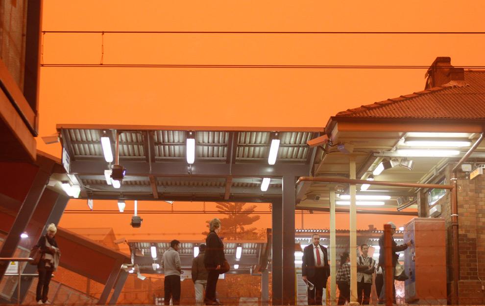 23) Люди, ожидающие поезда на станции, во время песчаной бури 23 сентября 2009, Сидней.(AP Photo/Rob Griffith)