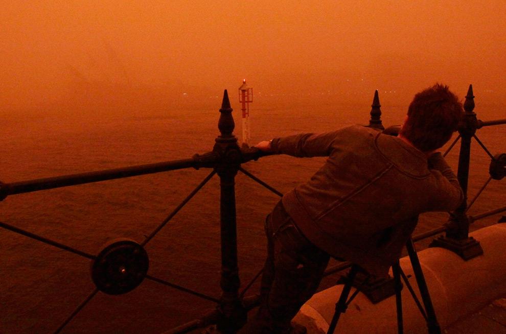 25) Мужчина пытается сделать фотографию едва заметного сквозь плотную завесу песка Сиднейского оперного театра, 23 сентября, 2009. (REUTERS/Tim Wimborne)