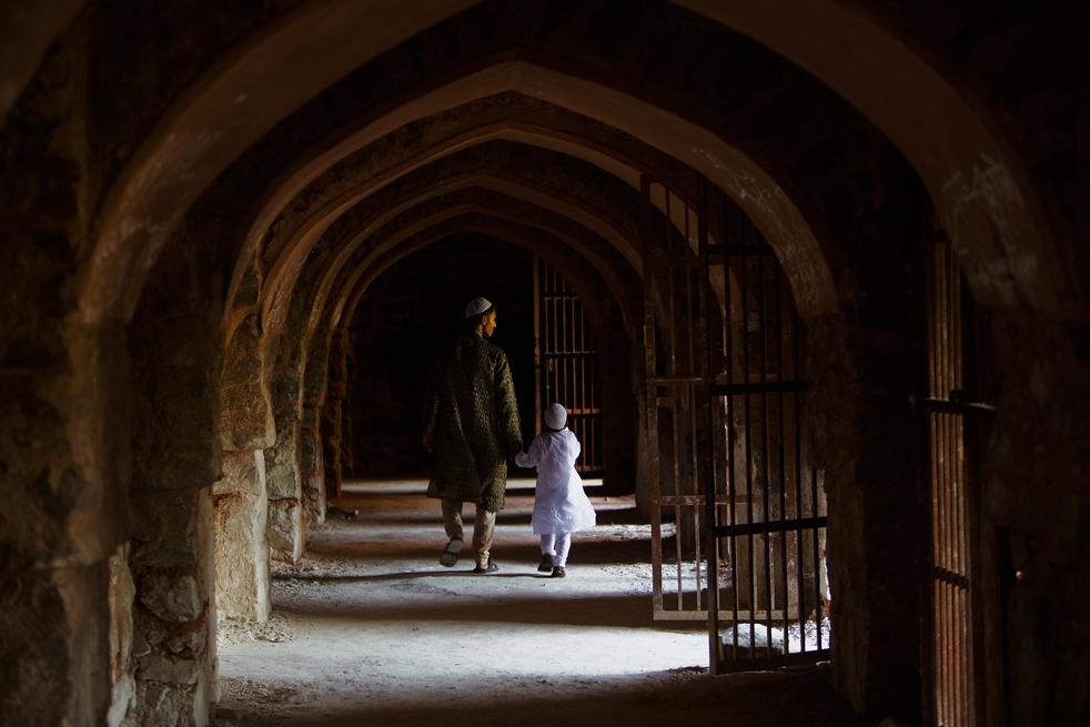 14) Индийский мужчина-мусульманин ведет мальчика по коридору в развалинах мечети Фероз Шах Котла после вознесения молитв Эйд-фитр на улице 21 сентября, в Нью-Дели, Индия. (Getty Images/Daniel Berehulak)