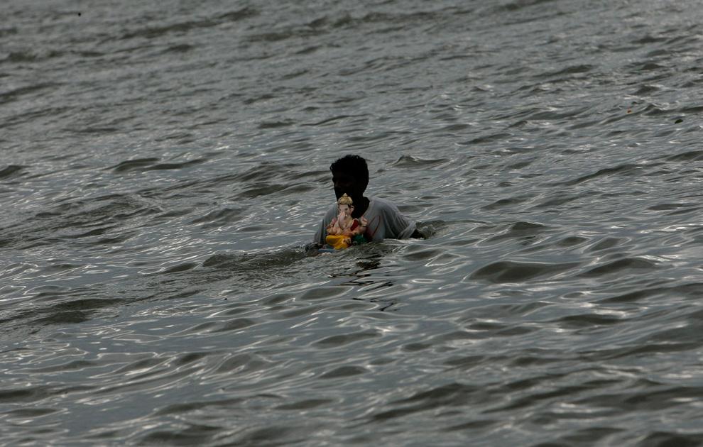 7. Индуист несет статую бога Ганеша, чтобы погрузить ее в воды Аравийского моря во время фестиваля Ганеш Чатуртхи в Мумбаи, Индия, в понедельник 24 августа 2009 года. (AP Photo/Rajanish Kakade)