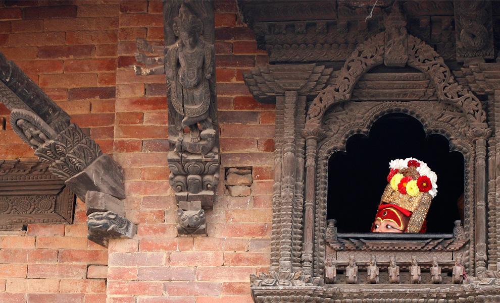 8. Мальчик в образе бога Ганеша – избавителя от преград – выглядывает из окна, перед тем как появиться на публике для поклонения во время фестиваля Индра Джарта в Катманду 3 сентября 2009 года. Неварское сообщество Непала начало празднование индуистского фестиваля Индра Джарта с поклонения Кумари – «живой богини» и богу дождя Индра. (REUTERS/Shruti Shrestha)