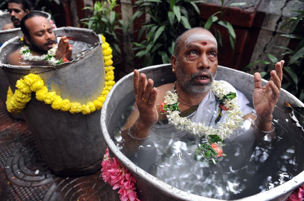9. Индуистские святые садху читают мантры и молитвы во время ритуала Варуна Яджна, чтобы ублажить бога дождя в Санкара Маттхам в Мумбаи, Индия, 26 августа 2009 года. 10 жрецов стоят в воде по шею в течение 4 часов и читают специальные молитвы, чтобы вызвать дождь. (INDRANIL MUKHERJEE/AFP/Getty Images)
