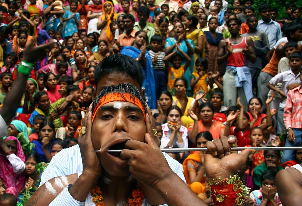 14. Идусу прокалывают рот во время ежегодной религиозной процессии под названием Шитла Мата в северном индийском городе Чандигарх 16 августа 2009 года. Во время этой процессии индусы подвергают себя болезненным ритуалам, чтобы продемонстрировать свою веру и раскаяние богам перед храмом богини Шитлы. (REUTERS/Ajay Verma)