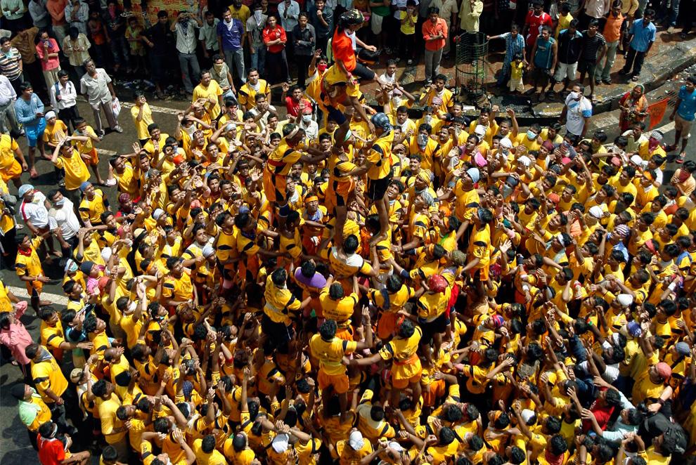 18. Индусы образуют живую пирамиду, чтобы достать глиняный горшок с маслом во время празднования Джанмаштами в Мумбаи 14 августа 2009 года. Джанмаштами символизирует рождение индийского бога Кришны. (REUTERS/Punit Paranjpe)