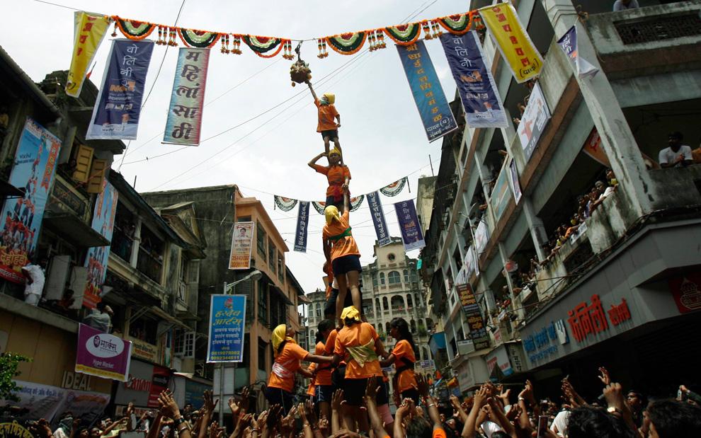 19. Женщины образуют живую пирамиду, чтобы разбить глиняный горшок с маслом во время Джанмаштами в Мумбаи 14 августа 2009 года. (REUTERS/Punit Paranjpe)