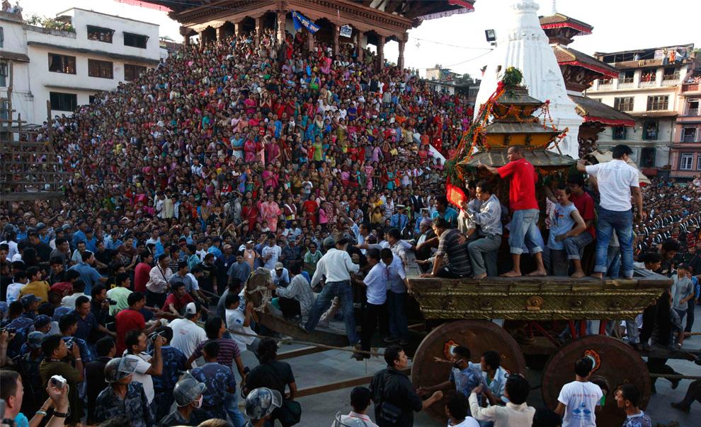 22. Непальские индуисты толкают повозку с живой богиней, известной здесь как «кумари» во время недельного фестиваля Индра Джатра на площади Дурбар в Катманду, Непал, в четверг 3 сентября. (AP Photo/Gemunu Amarasinghe)