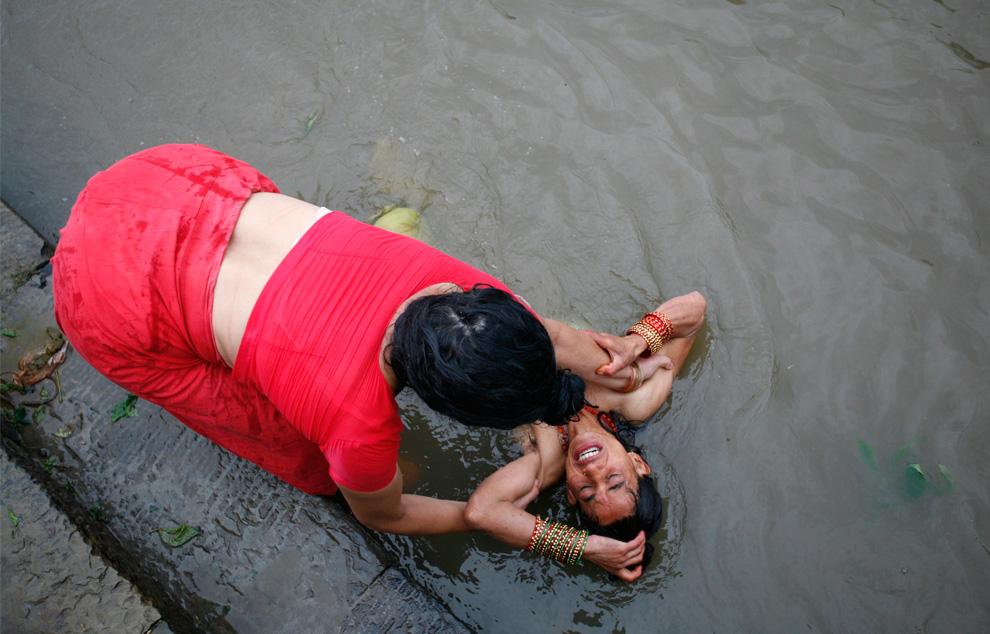 26. Индуистка на фестивале Риши Панчами помогает другу принять священные ванны в реке Багмати в Катманду 24 августа 2009 года. Во время фестиваля женщины почитают Сапта Риши (семь святых), принимая священные ванны, что символизирует избавление от всех грехов за весь год. (REUTERS/Shruti Shrestha)