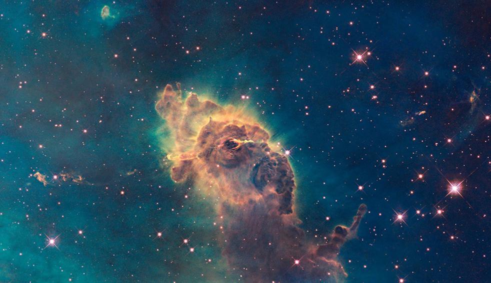 2. Космический телескоп Hubble сделал этот снимок, запечатлевший изображение газа и пыли; эта колонна находится в горячей звездной колыбели под названием Туманность Карина, расположенной в 7 500 световых лет от южного созвездия Карина. На снимке показано, что астронавты увидели более полный вид колонны и ее содержимого, когда отдаленные детали, не видимые до этого, стали ясными в инфракрасном диапазоне. Обжигающая радиация и скоростные ветры (потоки заряженных частиц) от этих звезд образуют колонну и заставляют возникать в ее пределах новые звезды. Сверху образования можно увидеть отходящие от него полоски газа и пыли. Снимок опубликован NASA в среду 9 сентября. (NASA)