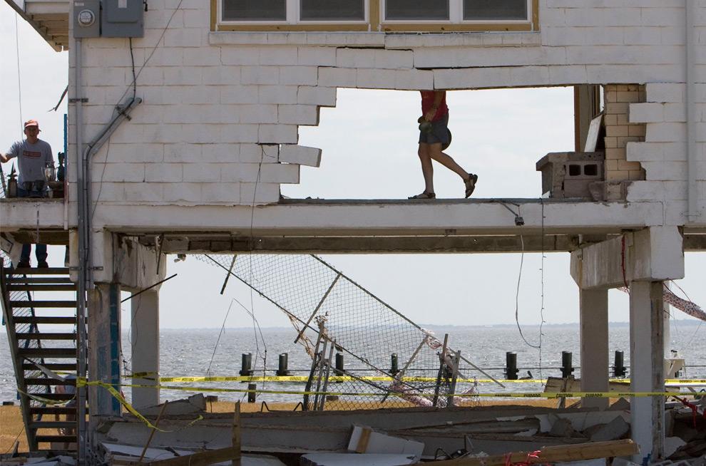 3а. Раллс Ли (в центре) спасает имущество в руинах морского клуба Сибрук после урагана Айк 20 сентября 2008 года в городе Сибрук, штата Техас. (AP Photo/Houston Chronicle, James Nielsen)