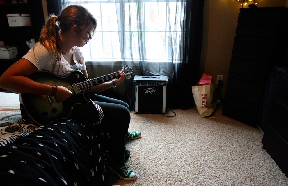 4б. Теперь уже 15-летняя Элисон играет на гитаре в среду 19 августа 2009 года на новенькой кровати в той же комнате. (AP Photo/Houston Chronicle, Mayra Beltran)