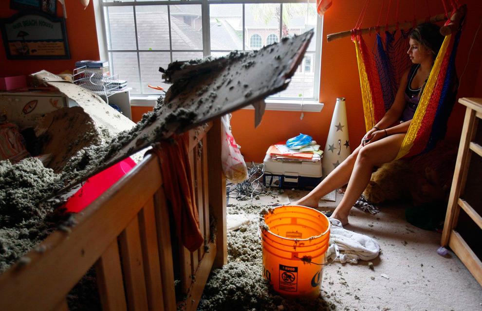 4а. 14-летняя Элисон Накин сидит среди беспорядка после того, как в ее комнате рухнула крыша из-за урагана Айк 13 сентября 2008 года в городе Перланд, штат Техас. (AP Photo/Houston Chronicle, Mayra Beltran)