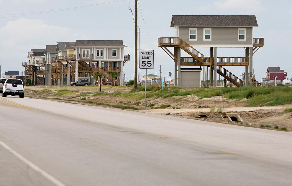 8а. На следующих двух снимках показаны «птичьи домики» (так их называют местные жители из-за дизайна) недалеко от Гилхриста, штат Техас. Эта фотография была сделана 16 сентября 2008 года: волны от урагана Айк принесли на 87-ое шоссе песок и обломки. (AP Photo/Tony Gutierrez)