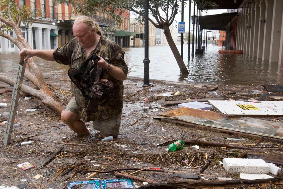 11а. Том ЛеКрой пробирается сквозь обломки на затопленной улице после урагана Айк в субботу 13 сентября 2008 года в Галвестоне, штат Техас. (AP Photo/Houston Chronicle, Brett Coomer)