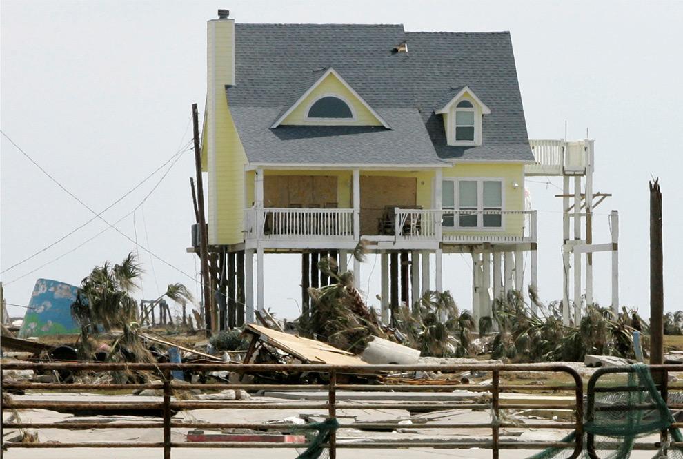 12а. Дом Пэм и Уоррена Адамс в Гилхристе, штат Техас, 16 сентября 2008 года. Этот дом стал знаменитым, так как единственный остался стоять в этом сильно поврежденном районе. (AP Photo/Tony Gutierrez)