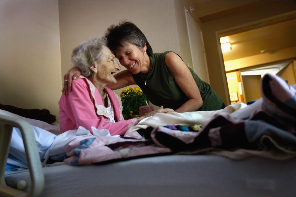 1. Массажист Никки Хернандес обнимает неизлечимо больную 83-летнюю Джеки Бетти после массажа в хосписе Святого Иоанна 21 августа в Лейквуде, штат Колорадо. (Getty Images/John Moore)
