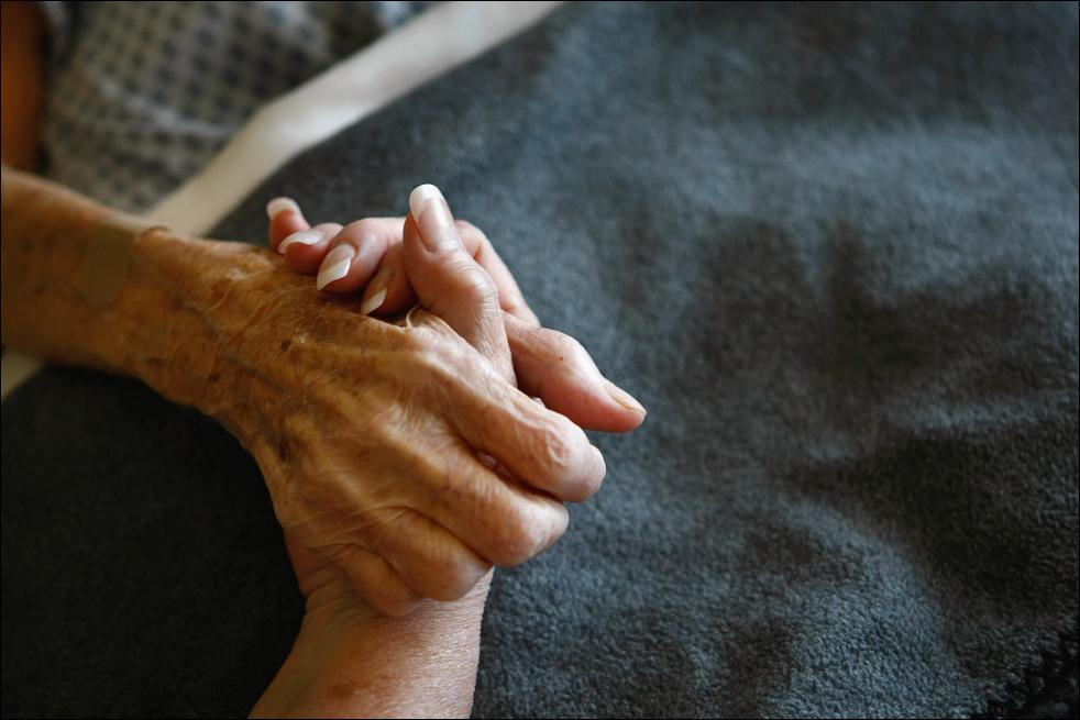 5. Неизлечимо больную пациентку хосписа Святого Иоанна успокаивают в ее постели. (Getty Images/John Moore)