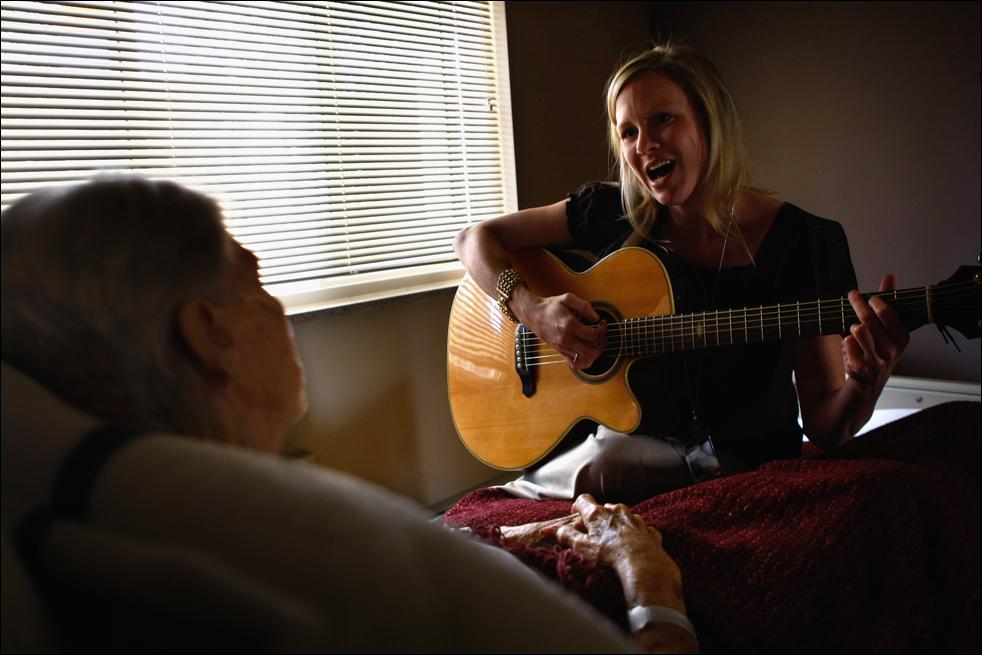 7. Джен Данлэп поет для неизлечимо больной 91-летней пациентки хосписа Эвелин Бронинг в хосписе Святого Иоанна 20 августа в Лейквуде, штат Колорадо. (Getty Images/John Moore)