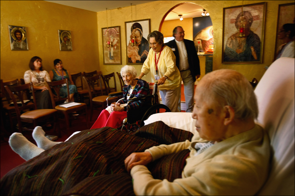12. Пациентку с неизлечимым диагнозом Хелен Кресс ввозят на инвалидном кресле в часовню для службы в хосписе Святого Иоанна 21 августа в Лейквуде, штат Колорадо. (Getty Images/John Moore)