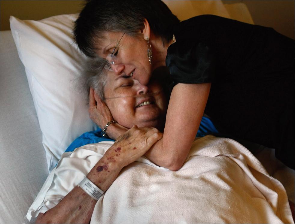 13. Массажист и ароматерапевт Никки Хернандез обнимает неизлечимо больную пациентку хосписа 68-летнюю Джудит Вагнер после сеанса массажа в хосписе Святого Иоанна 20 августа в Лейквуде, штат Колорадо. Вагнер, которой 4,5 года назад поставили страшный диагноз – рак – говорит так: «Все мы когда-нибудь уйдем. Просто кто-то на очереди первый». (Getty Images/John Moore)