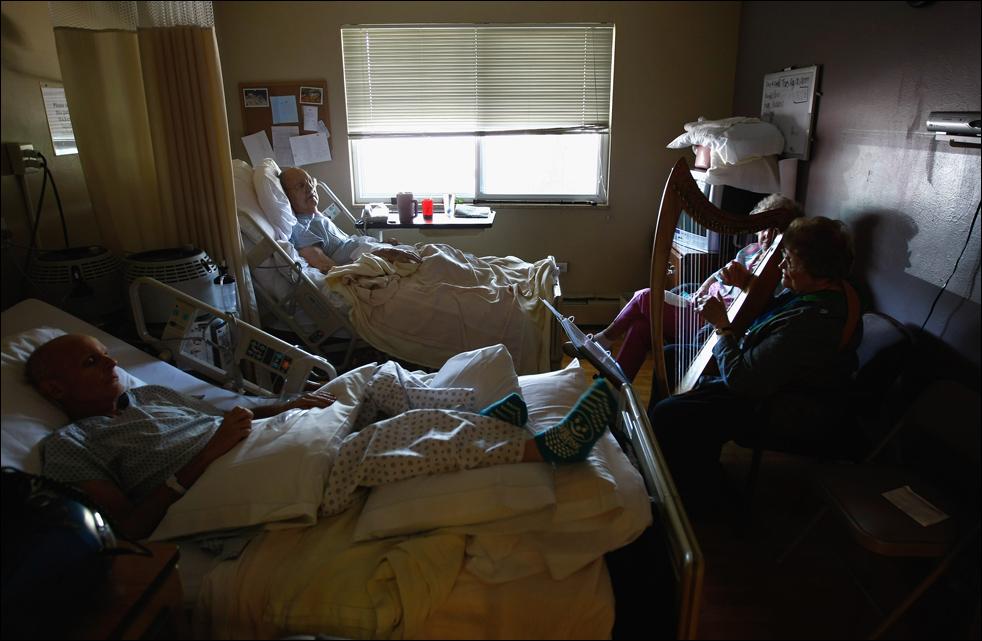 16. Арфистка Рокси Пипо (справа) играет для неизлечимо больных пациентов в хосписе Святого Иоанна 20 августа в Лейквуде, штат Колорадо. Арфатерапия, целью которой является «исцеление без лечения» - одна из бесплатных терапий, применяемых в хосписе. (Getty Images/John Moore)
