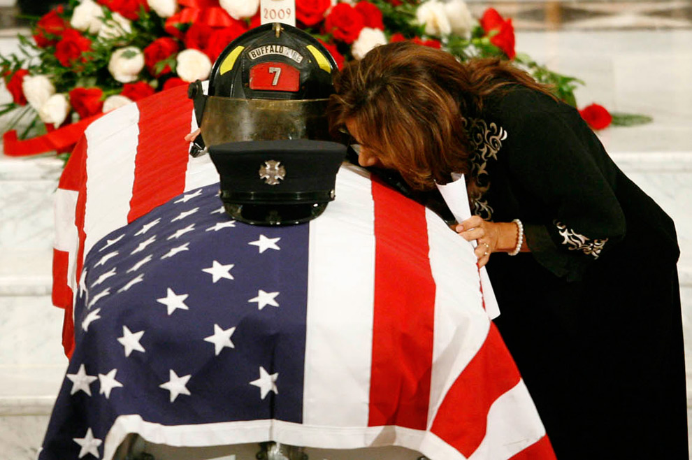 7. Энджи Хойсингер – мать пожарного Джонатана Крума – целует гроб сына после речи на панихиде в соборе святого Джозефа в Буффало, штат Нью-Йорк, в пятницу 28 августа 2009 года. Крум был одним из двух пожарных, погибших в понедельник 24 августа 2009 года, провалившись в подвал магазина, пытаясь спасти человека. (AP Photo/Harry B. Scull, J.R.)