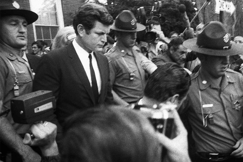 11. Сенатор Эдвард Кеннеди в сопровождении полиции покидает здание суда в Эдгартауне, Массачусетс, 25 июля 1969 года, после того как ему были предъявлены обвинения в том, что он покинул место несчастного случая, в результате которого погибла его секретарь Мэри Джо Копече. (AP Photo/File)