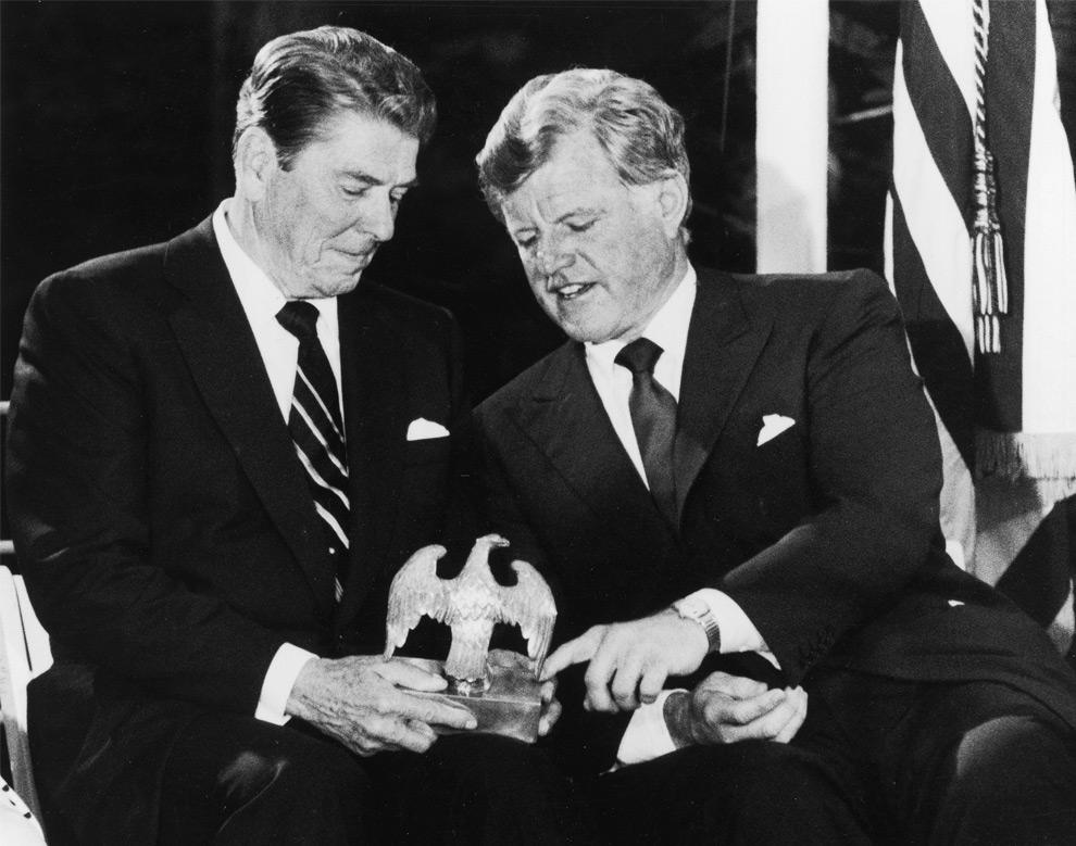 15. Сенатор Эдвард Кеннеди разговаривает с президентом Рональдом Рейганом (слева) 24 июня 1985 года, глядя на символ США – белоголового орлана, который украшал стол президента Джона Ф. Кеннеди. Снимок сделан во время сбора пожертвований на мемориальную библиотеку имени Джона Ф. Кеннеди в МакЛине, Вирджиния. (AP Photo/Charles Tasnadi)