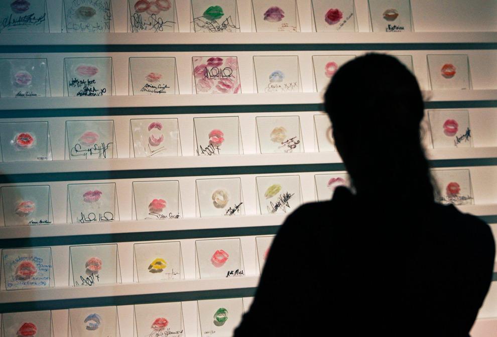 16. Девушка смотрит на галерею подписанных губной помадой «сувениров» от звезд модельного бизнеса, включая Кейт Мосс, во время пресс-релиза выставки SHOWStudio:Fashion Revolution в Лондоне 15 сентября 2009 года. (REUTERS/Luke MacGregor)