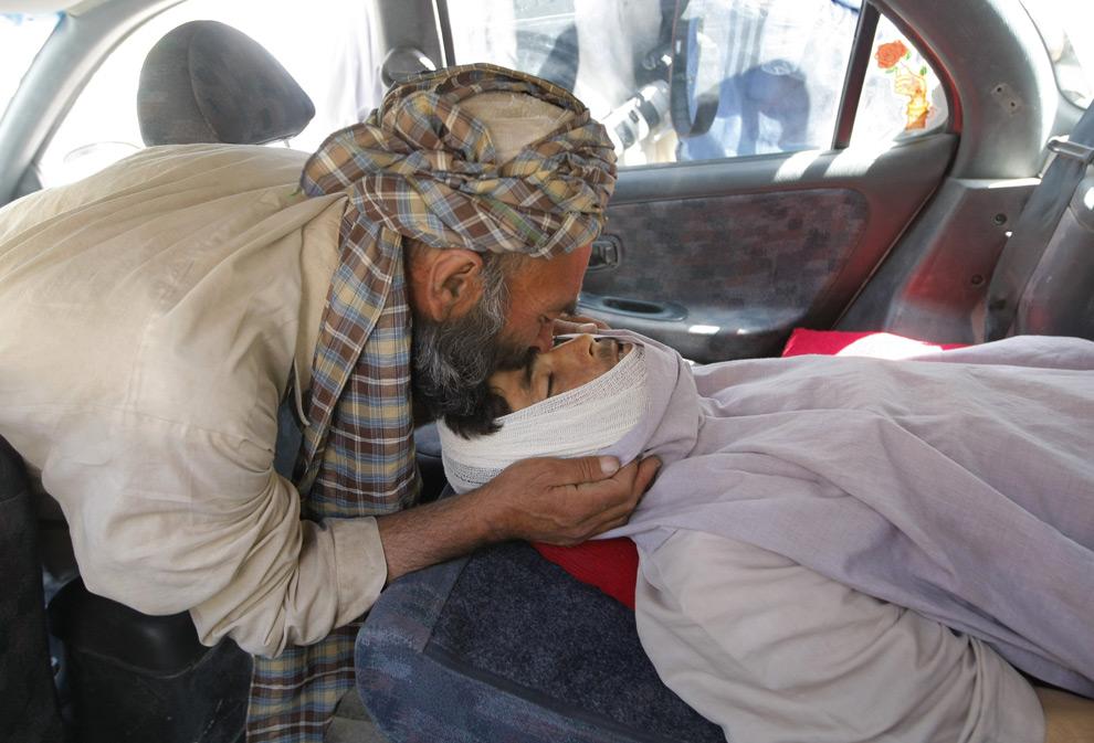 23. Мохаммад Найем целует в автомобиле у больницы Герата тело своего сына Бесмелла, которого якобы убили западные военные силы во время воздушного обстрела деревни Саивошан к востоку от Герата в Афганистане, 17 августа 2009 года. (BEHROUZ MEHRI/AFP/Getty Images)