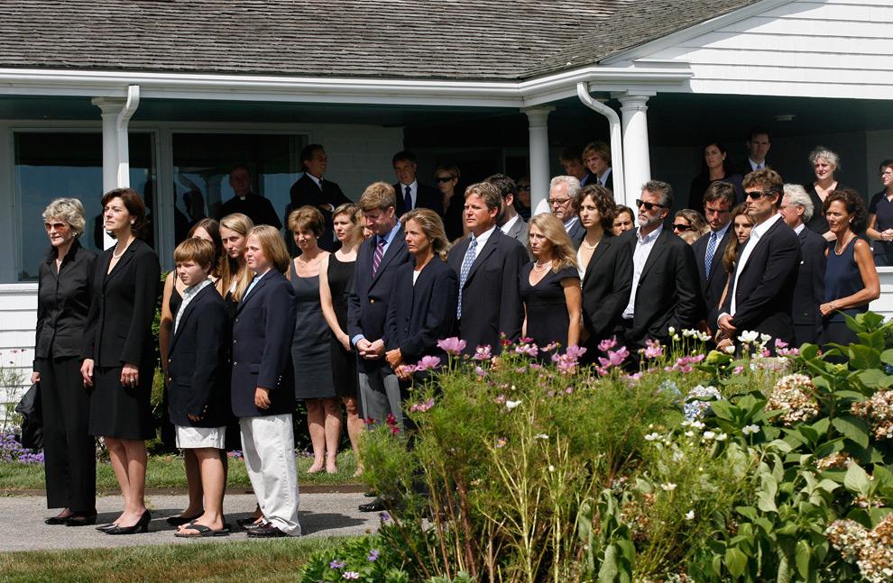 27. Семья и друзья покойного сенатора Эдварда Кеннеди смотрят, как гроб с его телом погружают в катафалк в поместье Кеннеди в порту Хианннис, Массачусетс, 27 августа 2009 года. (STEW MILNE/AFP/Getty Images)