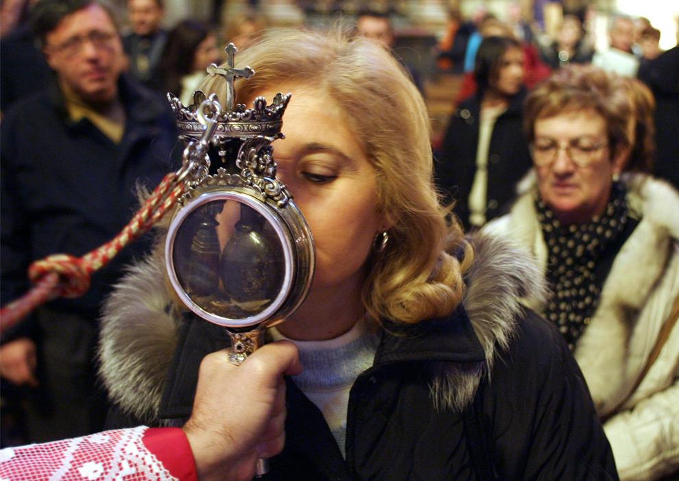 30. Женщина целует фиал с тем, что местные римские католики считают кровью святого Януария в Неаполе 16 декабря 2006 года. Позже в этом же месяце страх заразиться вирусом H1N1 заставит верующих прекратить свой ритуал с поцелуем. Решение приостановить ритуал поцелуя колбочки с кровью святого было неохотно принято духовенством и городскими властями в понедельник и стало жертвой нападок со стороны местных политиков. (REUTERS/Renato Nicois/Agnfoto)