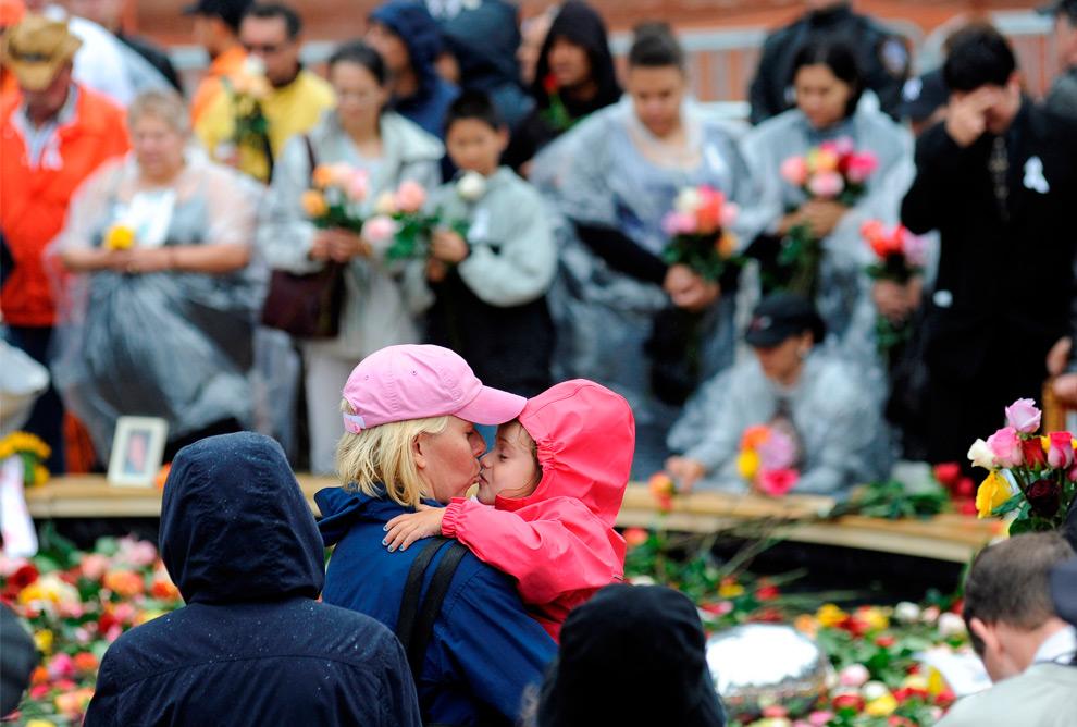 31. Женщина целует ребенка рядом с бассейном на нулевой отметке на церемонии, посвященной восьмой годовщине терактов 11 сентября 2001 года в Нью-Йорке в пятницу 11 сентября 2009 года. (AP Photo/David Handschuh)