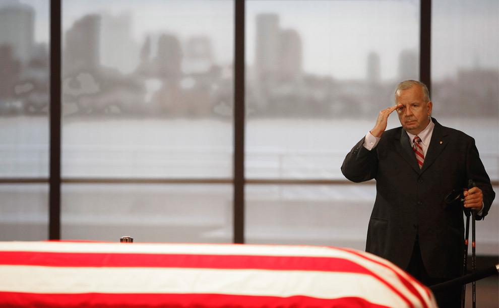 33. Участники похоронной процессии отдают честь на фоне серого бостонского горизонта у обернутого национальным флагом гроба сенатора Эдварда Кеннеди в Бостоне в пятницу 28 августа 2009 года. (AP Photo/Stephan Savoia)