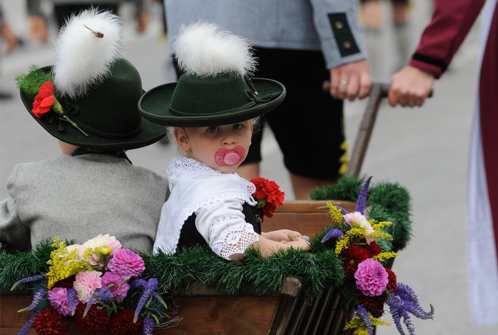 4. Лолло и Лука сидят в повозке в традиционных костюмах на параде Октоберфест в Мюнхене, Германия, в воскресенье 20 сентября 2009 года. (AP Photo/Christof Stache)