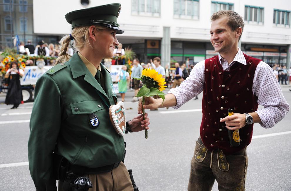 11. Молодой человек дарит девушке-полицейскому цветок во время парада в честь фестиваля пива Октоберфест 20 сентября 2009 года в Мюнхене, Германия. (JOE KLAMAR/AFP/Getty Images)