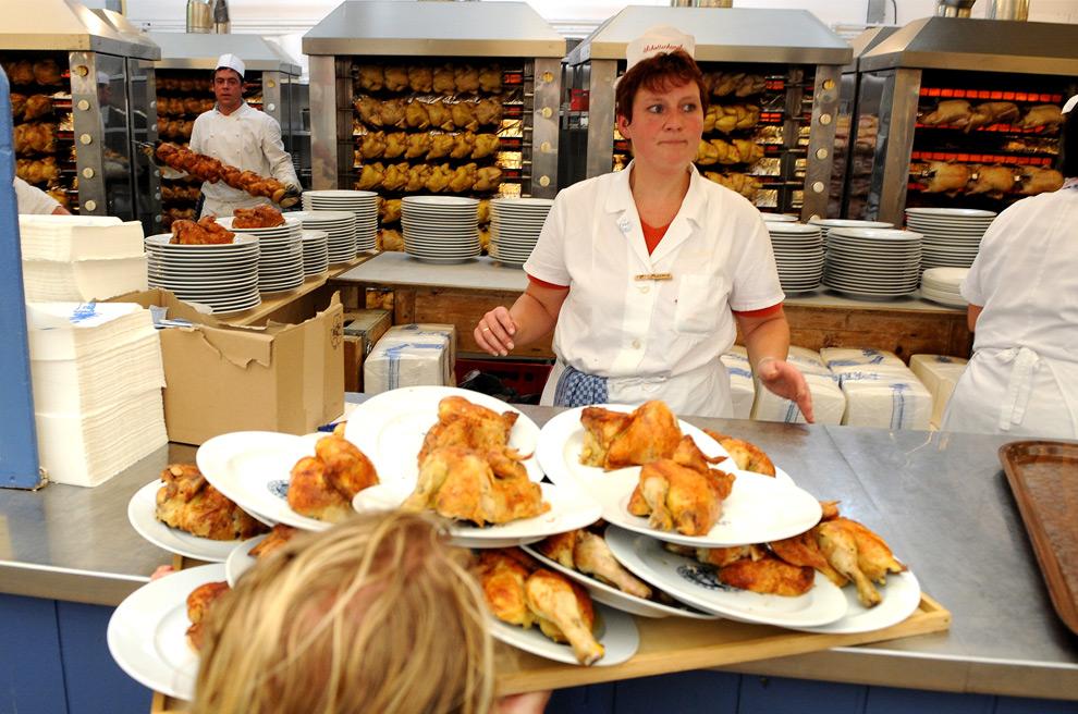 14. Официантка забирает поднос с курицей из кухни на празднике пива Октоберфест 19 сентября 2009 года в Мюнхене. (JOE KLAMAR/AFP/Getty Images)