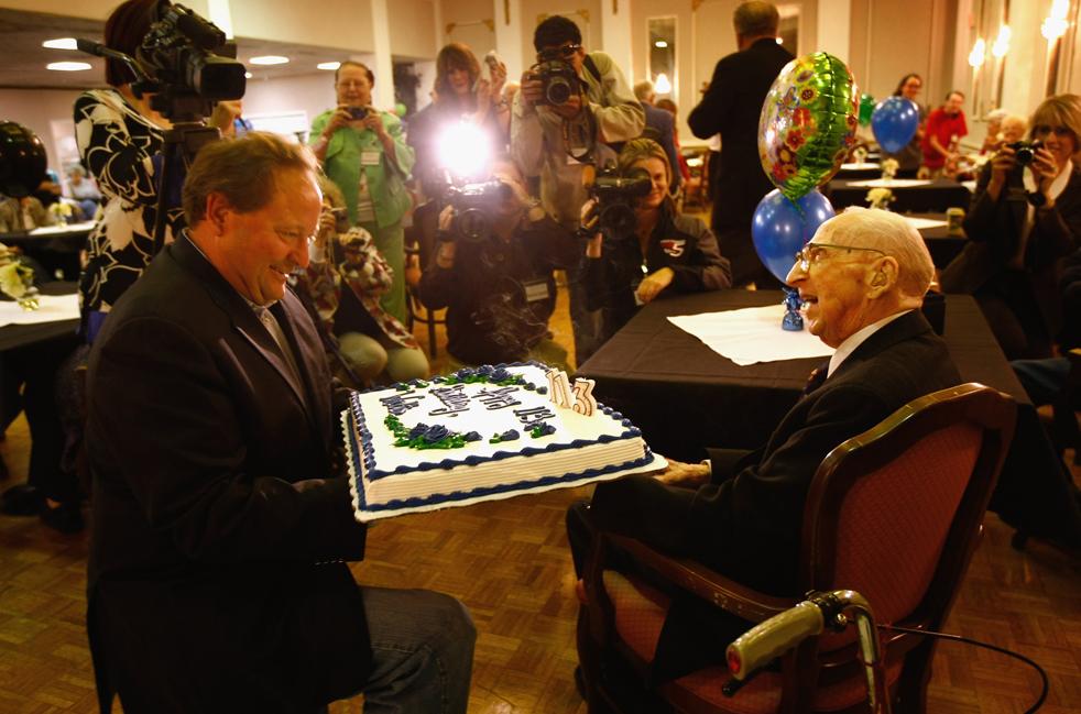 1) Губернатор Монтаны Брайан Швейцер, слева, держит торт, приготовленный к 113-му дню рождения Уолтера Бреунинга. Снимок сделан во время празднования дня рождения в доме для престарелых в Грейт-Фолсе. Бреунинг родился 21 сентября 1896, в Мелроуз, штат Миннесота, и получил звание «самый старый человек в мире», после того, как англичанин Генри Аллингхам скончался в июле прошлого года 18. (Getty Images/John Moore)
